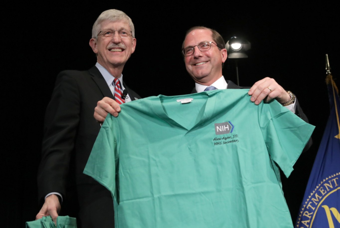 Secretary Azar holding an NIH surgeon's scrubs with his name embroidered on it.