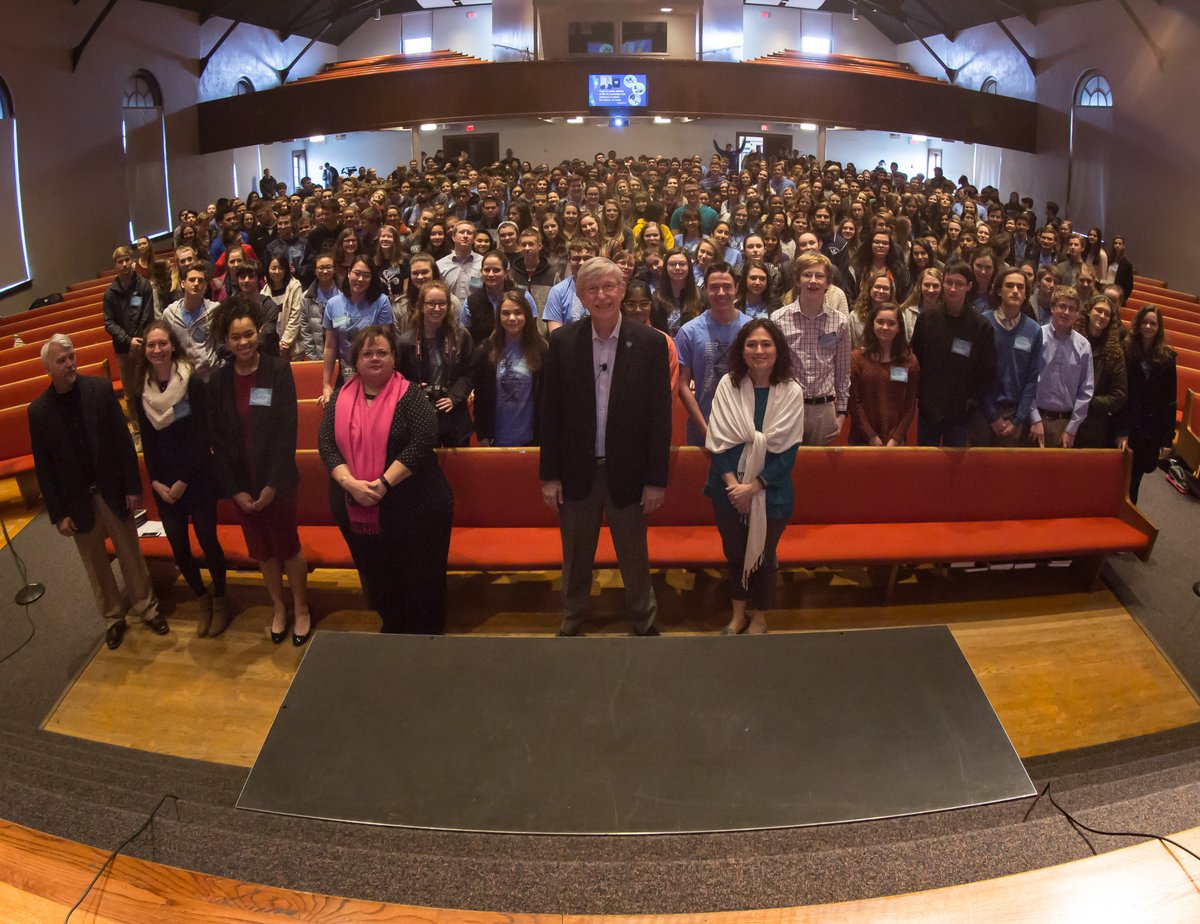 Francis Collins standing in an auditorium full high school students.