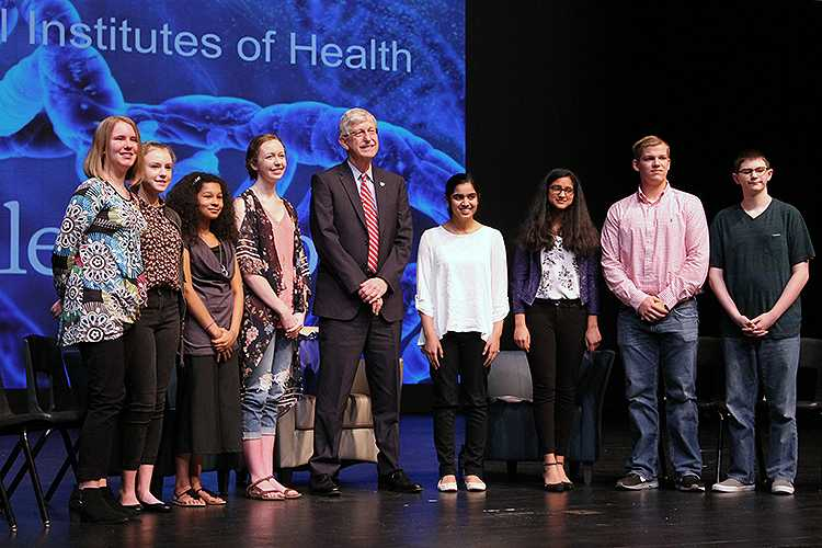 Francis Collins standing with a teacher and students from Bentonville High School
