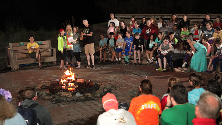 Dr. Francis Collins sings for children around a campfire at Camp Fantastic