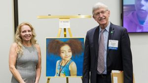 Dr. Francis Collins and Patricia Weltin unveil a portrait of a little girl with a rare disease